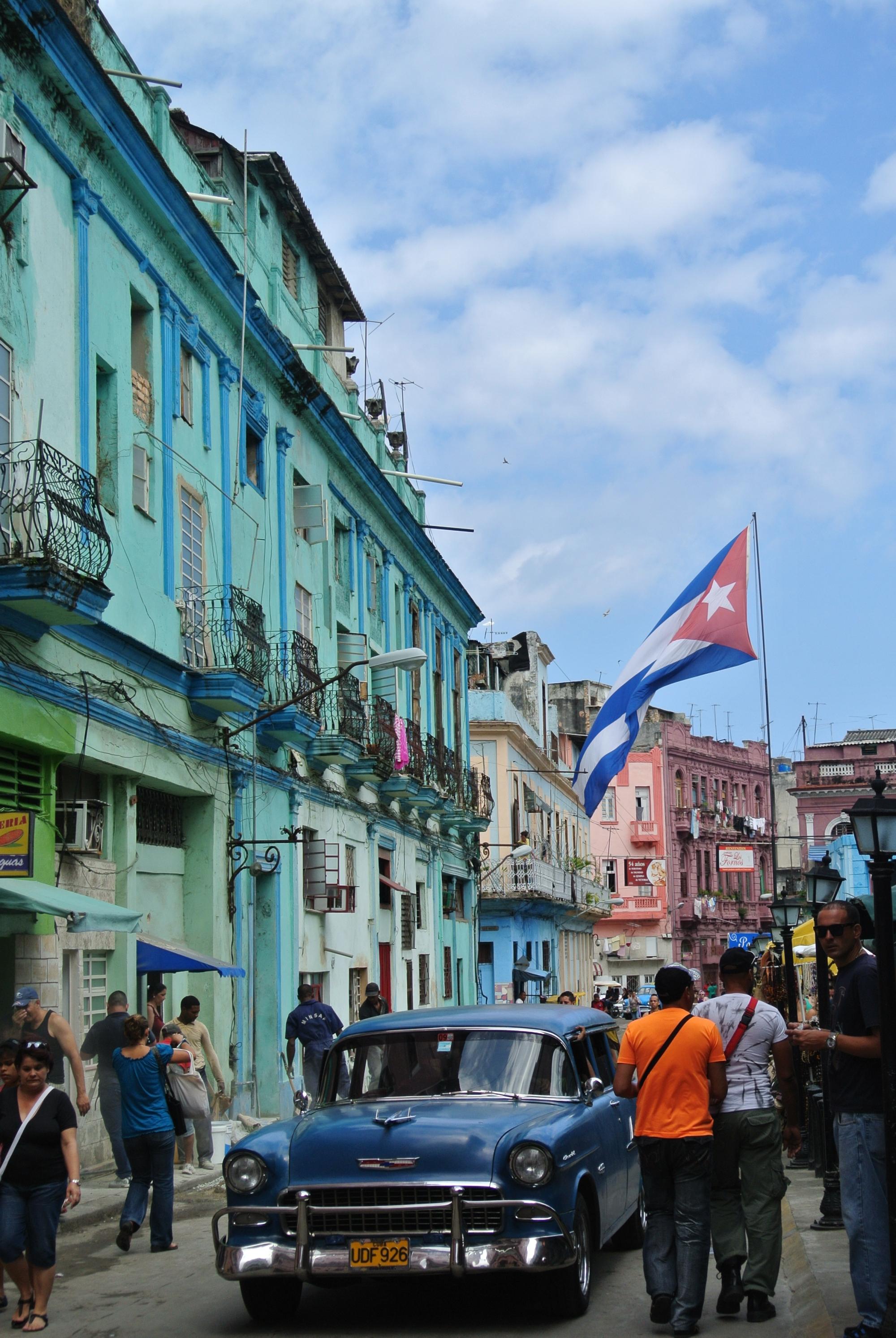 Blue vintage car, Cuba flag flying high in Havana