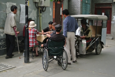 A group of elders playing cards in the Hutong district, Beijing