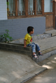 Little boy sitting alone in a Hutong street in Beijing