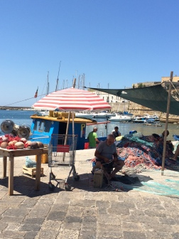 Fisherman fixing nets at Gallipoli harbour, Puglia, Italy