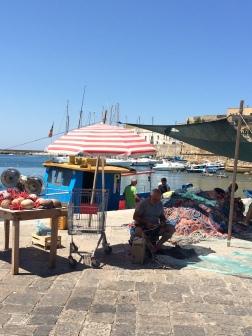 Fisherman fixing nets at Gallipoli harbour, Puglia, Italy